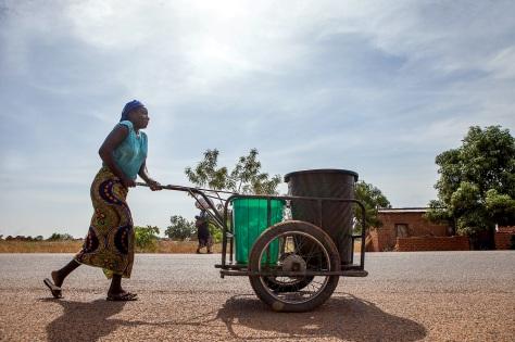 Une femme pousse des bidons d'eau depuis le Centre de Santé de Bologo. Le centre est un des lieux de distribution de moustiquaires de la campagne. Global Fund/2014/Esiebo