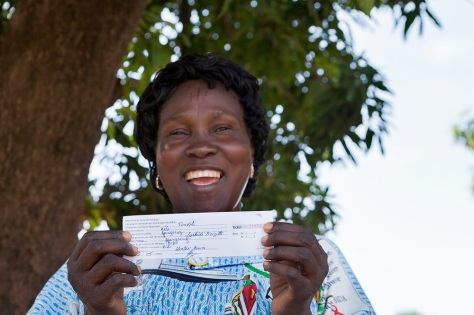 Mme Brigitte aves son ticket pour une moustiquaire gratuite. Elle ira au centre de santé pour la distribution le lendemain. Global Fund/2014/Esiebo