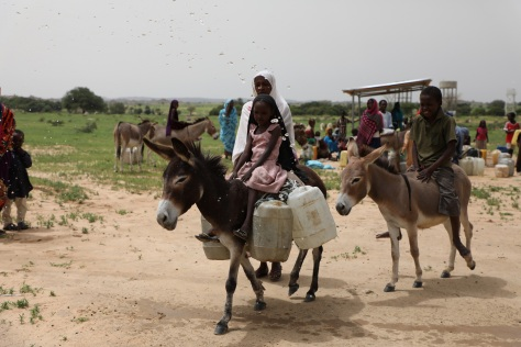 Beneficiaries leaving the water pump station N'2_ and water tower at their back