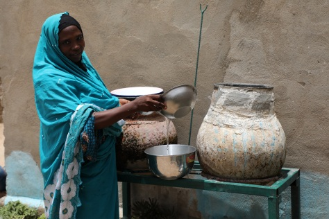 Khadidja fetching water from a jar at her house